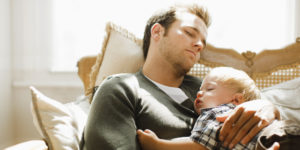 Father napping with son on sofa